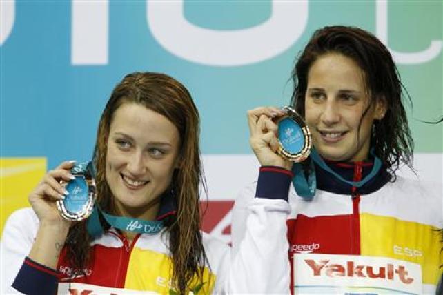 Excelente jornada para los nadadores españoles el jueves en el campeonato del mundo en piscina corta que se está disputando en Dubái, ya que Mireia Belmonte sumó su tercera medalla - una plata - a los dos oros del miércoles en la misma prueba que ganó Erika Villaécija, los 800 libres, mientras que Aschwin Wildeboer se llevó el bronce en los 100 metros espalda. Imagen de Villaecija (dcha.) y Belmonte en el podio de Dubái el 16 de diciembre. REUTERS/Rabih El Moghrabi