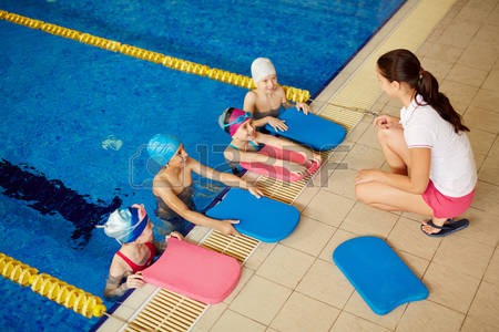 58574253-kids-with-swimboards-listening-to-their-coach